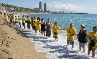 Menselijke keten als protest tegen het toerisme op het strand van Barcelona