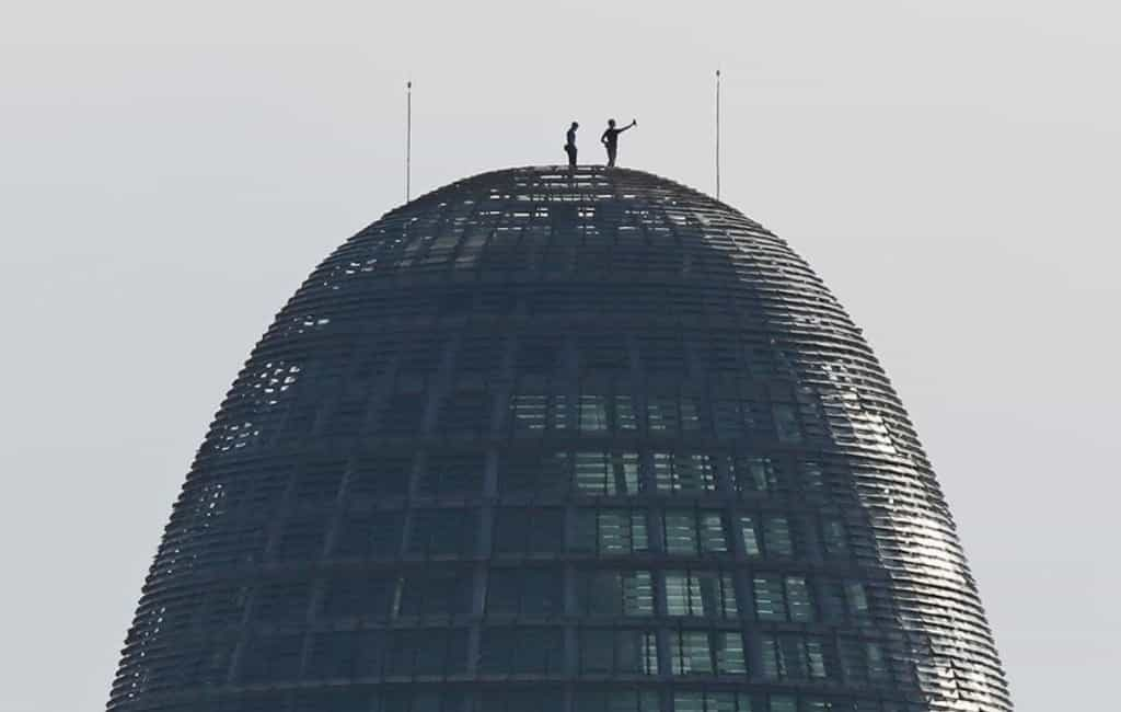 Twee mannen beklimmen de Torre Glòries in Barcelona voor een selfie